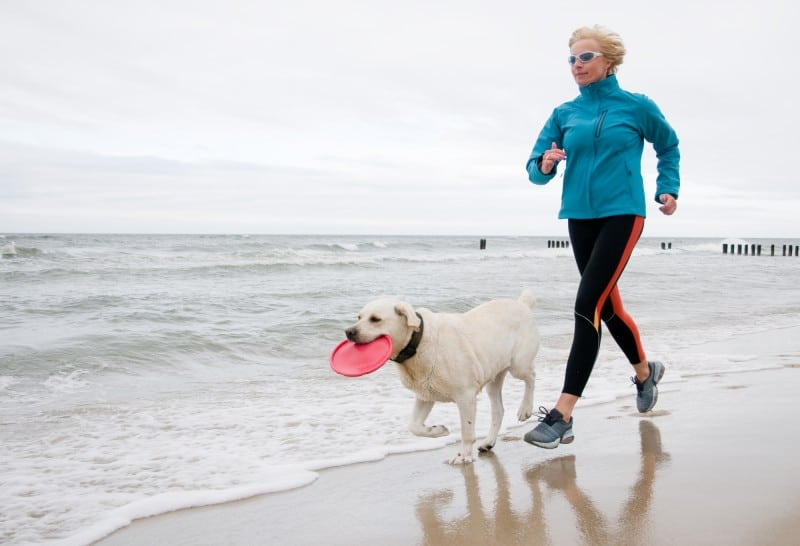 Woman running with dog at beach
