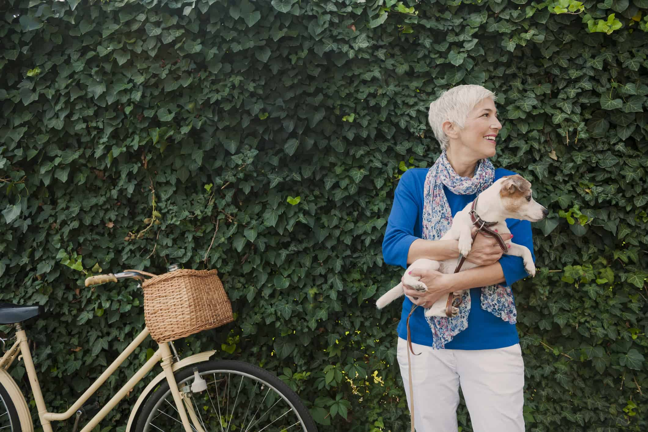 mature woman holding dog, leaves behind them and bicycle